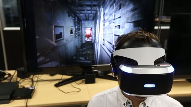 A visitor tries out a Sony Computer Entertainment Inc PlayStation VR headset demonstrating the Resident Evil 7 Biohazard VR game at the company's...
