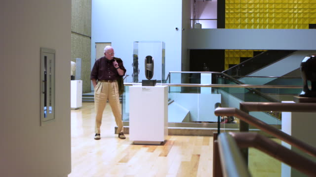 ws visitor walking around and looking at art sculpture in exhibit case in modern museum environment featuring hardwood floors / palm springs, california, usa - art gallery stock videos and b-roll footage