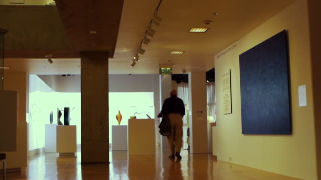 WS Visitor walking from gallery featuring modern paintings into gallery featuring contemporary art glass / Palm Springs, California, USA