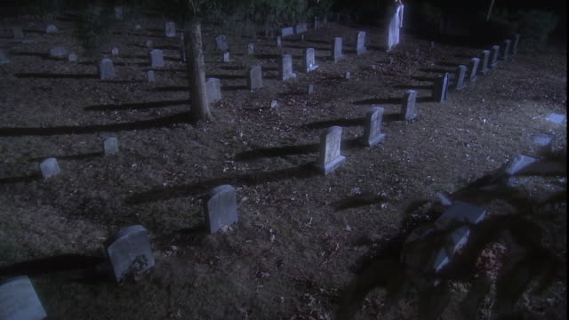 a visitor walks between the headstones of a spooky cemetery at golden hour. - mourning stock videos & royalty-free footage