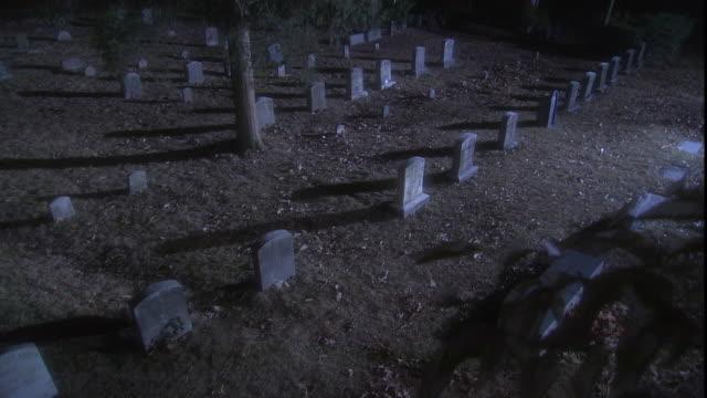 vidéos et rushes de a visitor walks between the headstones of a spooky cemetery at golden-hour. - cimetière