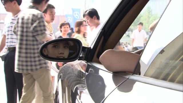 Visitors admiring sports cars at Beijing Car Show INT Car show visitors looking at silver Porsche as model wearing porsche baseball cap sits inside...