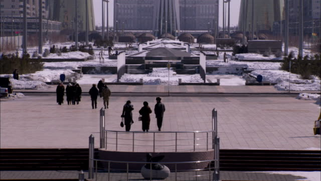 visitors and tourists make their way to the bayterek which features a spherical observation gallery in astana kazakhstan. available in hd. - kazakhstan stock videos & royalty-free footage
