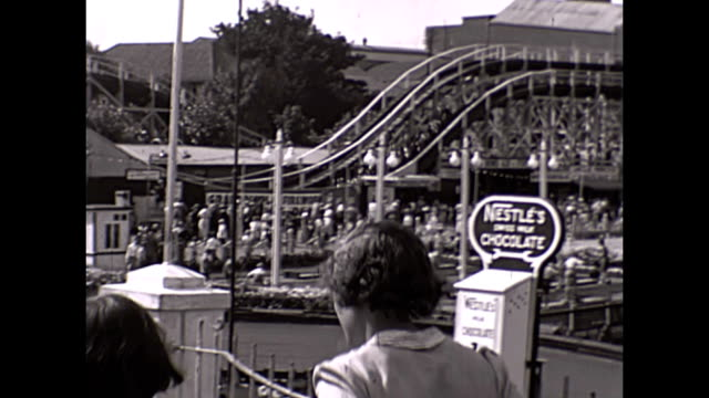 vidéos et rushes de visitors at dreamland margate uk 1938 / aeroplane exhibition / pov in vintage rollercoaster / crowds and general views including chocolate vending... - exposition et salon professionnel
