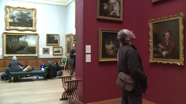 visitors at dulwich picture gallery peer at the old masters on the walls trying to spot the $120 chinese replica hung among paintings by rembrandt... - dulwich stock videos & royalty-free footage