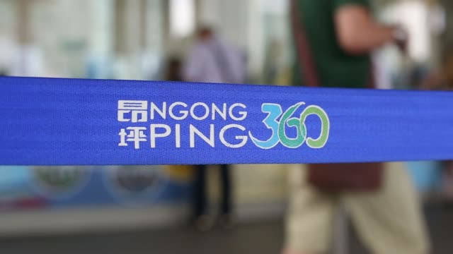 visitors at ngong ping 360 queuing up to purchase cable car tickets with ngong ping logo on a band in the foreground ngong ping 360 logo on a strap... - shop sign stock videos and b-roll footage
