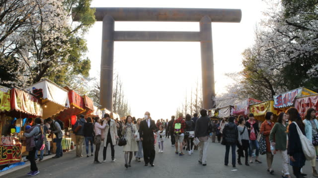 Visitors at Yasukuni Shrine in the evening sun under the arch with stands on both sides, Tokyo, Japan
