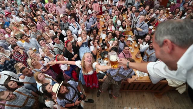 Visitors celebrate in a beer tent on the opening day of the 2018 Oktoberfest beer festival on September 22 2018 in Munich Germany
