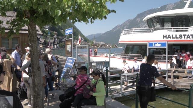 visitors disembarking boat at hallstatt village, salzkammergut, austrian alps, austria, europe - アッパーオーストリア点の映像素材/bロール
