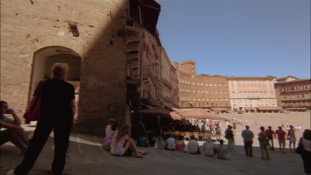 visitors enjoy the piazza del campo near torre del mangia and palazzo pubblico in siena, tuscany, italy. - piazza del campo stock videos and b-roll footage