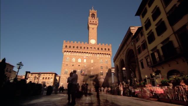 vídeos de stock e filmes b-roll de visitors enjoy the spectacular palazzo vecchio and loggia dei lanzi in florence, tuscany, italy. - florença