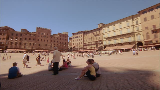 visitors enjoy the spectacular plaza beneath the torre del mangia and palazzo pubblico in siena, tuscany, italy. - palazzo pubblico stock videos and b-roll footage