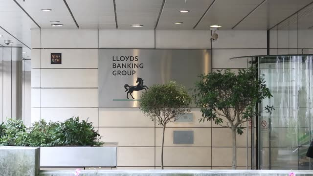 visitors enter and exit the lloyds banking group plc's headquarters in london uk on tuesday sept 17 a logo sits on a sign outside lloyds banking... - banking sign stock videos & royalty-free footage
