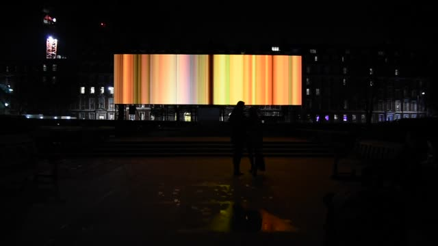 visitors gather by spinning night in living colour by artist elaine buckholtz as it is exhibited in grosvenor square during the lumiere london... - ナイトイン点の映像素材/bロール