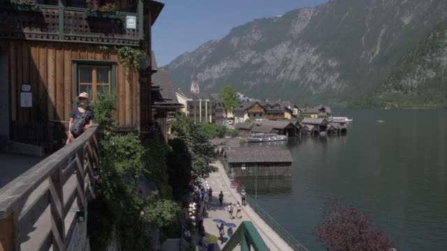 visitors, hallstatt lake and hallstatt village, unesco world heritage site, salzkammergut, austrian alps, austria, europe - アッパーオーストリア点の映像素材/bロール