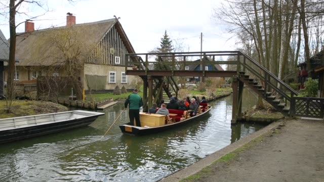 Visitors in canoes paddle on a canal past houses in the Spreewald region on April 5 2018 in Luebbenau Germany The Spreewald is a thicklyforested...