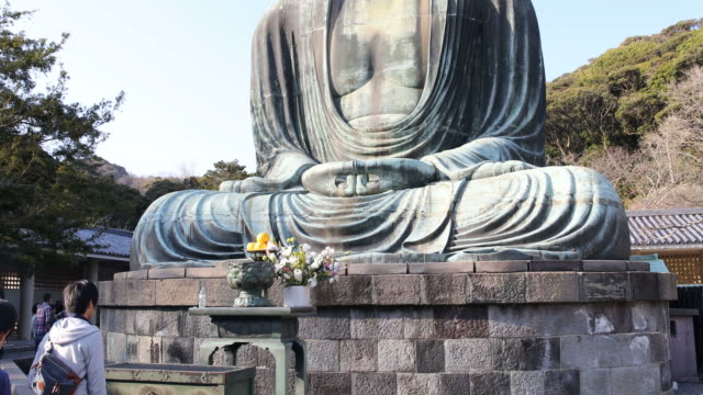 visitors in front of  the huge buddha statue at kotoku-in in the city of kamakura in kanagawa prefecture, japan - male likeness stock videos & royalty-free footage