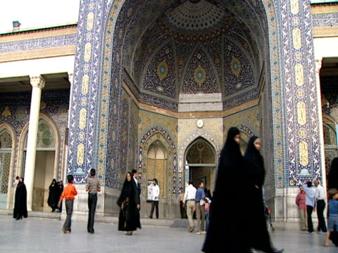 vidéos et rushes de visitors in modern and traditional dress entering and passing by entrance to iwan of mosque / qom, iran - format vignette
