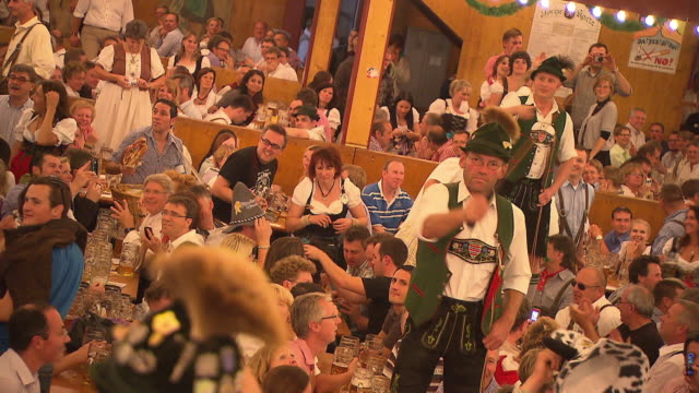 visitors in  the beer tent, men hit whip - bavaria stock videos & royalty-free footage