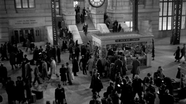 visitors linger at newsstands and pass through the lobby at pennsylvania station in new york city in 1941. - 1941 stock videos & royalty-free footage