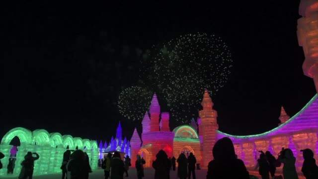 visitors look at ice sculptures during the annual harbin ice and snow festival in china's northeast heilongjiang province - schneefestival stock-videos und b-roll-filmmaterial