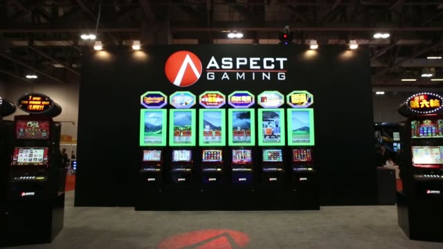 Visitors look at slot machines on display during the Macao Gaming Show in Macau China on Thursday Nov 14 Visitors walk through exhibition hall Slot...