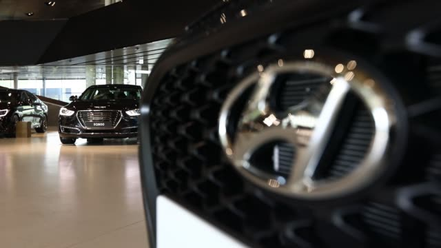 visitors look at vehicles on display at the hyundai motor co motorstudio showroom in goyang south korea on friday july 14 pan right to left visitors... - goyang stock videos and b-roll footage