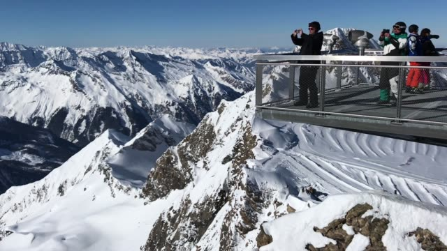 visitors look out from the nationalpark gallery viewing platform over the high tauern mountain range and glaciers from kitzsteinhorn mountain in the... - tyrol state austria stock videos and b-roll footage
