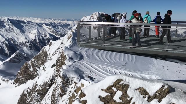 Visitors look out from the Nationalpark Gallery viewing platform over the High Tauern mountain range and glaciers from Kitzsteinhorn mountain in the...