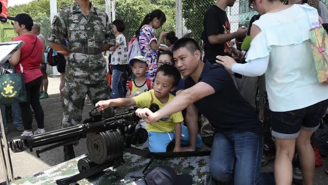 """""""visitors look through the scope of a machine gun as they attend an open day at the ngong suen chau barracks of people's liberation army at an open... - hong kong flag stock videos & royalty-free footage"""