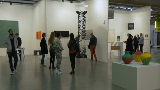 visitors looking at artworks at miart, a fair of modern and contemporary art on april 10, 2016 in milan . - miart stock videos & royalty-free footage