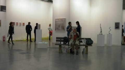 visitors looking at artworks at miart, a fair of modern and contemporary art on april 10, 2016 in milan . - miart 個影片檔及 b 捲影像
