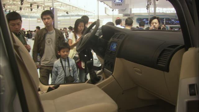 MS Visitors looking at hybrid car at Beijing Auto Show, Beijing, China