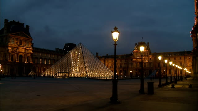 visitors mill around the plaza of the louvre at night. - louvre stock videos and b-roll footage