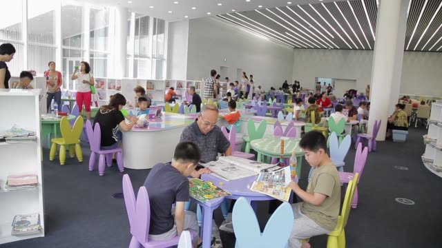 Visitors of all ages gather around tables at Tianjin Library.
