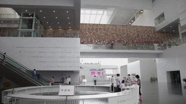 Visitors of Tianjin Library ride escalators in the lobby.