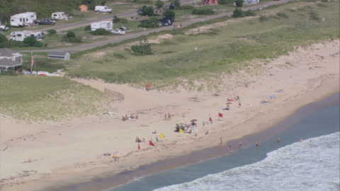 vidéos et rushes de aerial visitors on the sandy beach and swimmers in the water as waves are rolling in / east hampton, new york, united states - long island