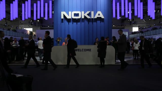 Visitors pass the Nokia Oyj pavilion at the Mobile World Congress in Barcelona A visitor tests a Nokia tablet device at the Nokia Oyj pavilion and...