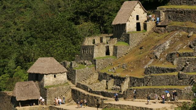 visitors pass through the guard houses at peru's machu picchu. - マチュピチュ点の映像素材/bロール