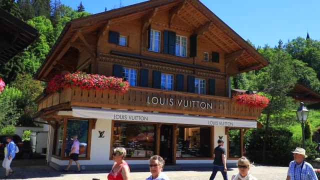 visitors passe next to french luxury fashion house louis vuitton storefront on the promenade, a pedestrian street with luxury, food and artisan shops... - fashionable stock videos & royalty-free footage