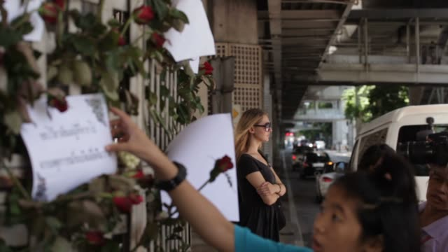 Visitors pay their respects at a memorial wall for those who died in the bombing near the Erawan Hindu shrine in Bangkok Thailand on August 17th 2015...