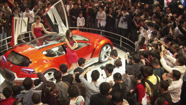 ws ha visitors photographing sports car at beijing auto show, beijing, china - 展覧会点の映像素材/bロール