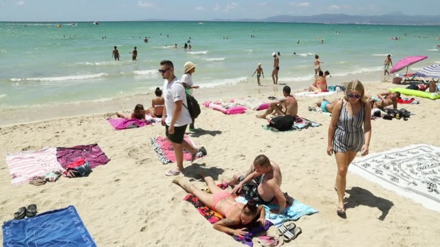 visitors relax at the beach along the ballermann stretch on july 27, 2017 in palma de mallorca, spain. the term ballermann, which combines the... - sunbathing stock-videos und b-roll-filmmaterial