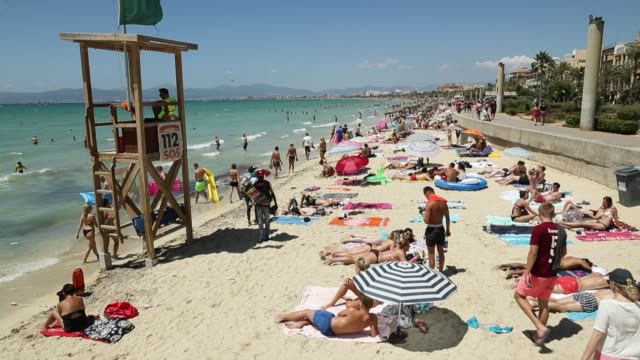 Visitors relax at the beach along the Ballermann stretch on July 27 2017 in Palma de Mallorca Spain The term Ballermann which combines the Spanish...