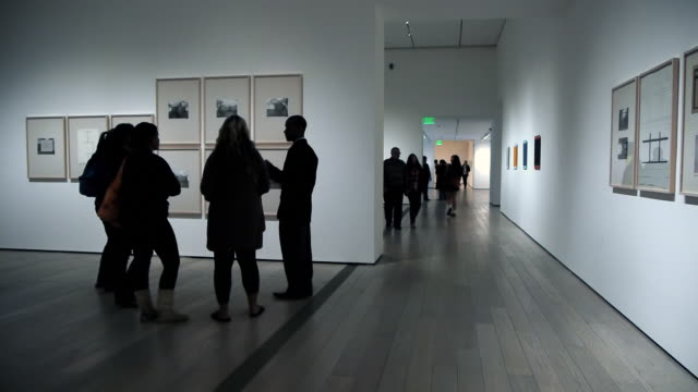 WS Visitors silhouetted against white walls and exhibited photography art in museum / Los Angles, California, USA