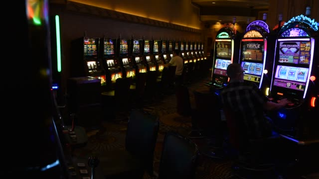visitors sit at slot machines on the casino floor inside the mgm resorts international grand hotel casino in las vegas nevada us on tuesday feb 16... - casino sign stock videos & royalty-free footage
