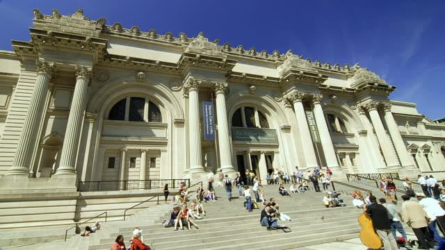 vídeos y material grabado en eventos de stock de  t/l visitors sitting on the steps and entering the metropolitan museum of art / new york city, new york, united states - met