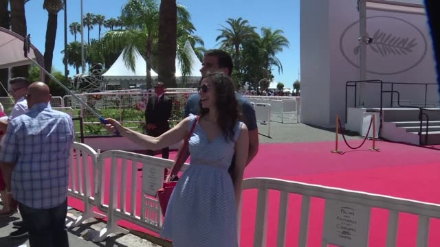 visitors to cannes enjoyed sunny skies and warm temperatures saturday whether searching for invitations to screenings or just taking selfies in front... - festival poster stock videos & royalty-free footage