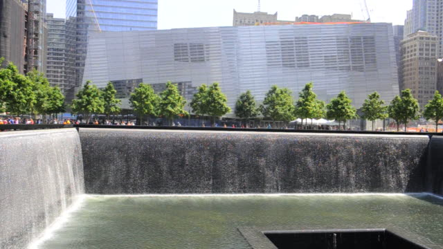 visitors to the 9/11 memorial watch water cascade into a recessed pool. - memorial stock videos and b-roll footage