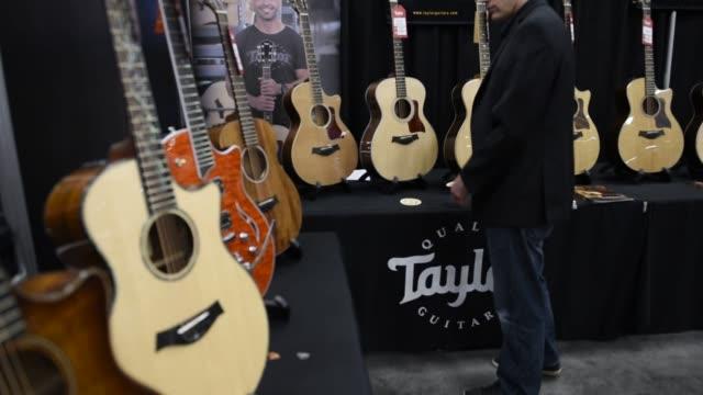 vídeos y material grabado en eventos de stock de visitors to the south by southwest interactive festival play acoustic guitars at the taylor guitars kiosk in austin, texas, shots pan up and down the... - estilo de música
